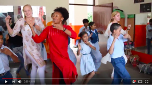 children and student-athletes dancing in a classroom