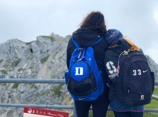 female student athletes hugging looking at mountain backs turned to us
