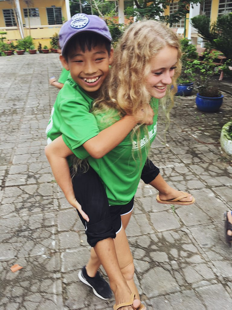 ACE Student-Athlete Giving Camper a Piggyback Ride