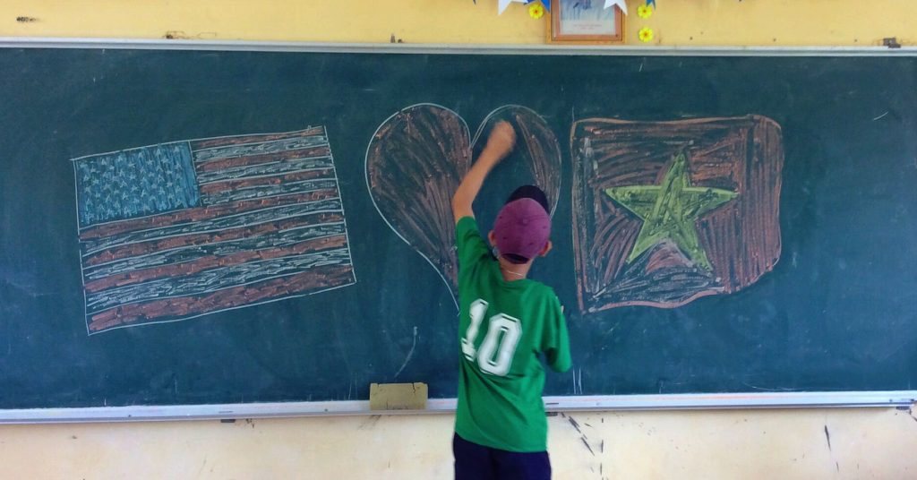 Student drawing a heart on a chalk board