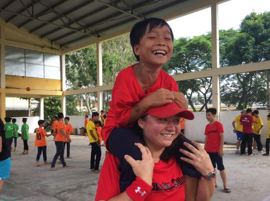 female student athlete giving laughing child a piggyback ride