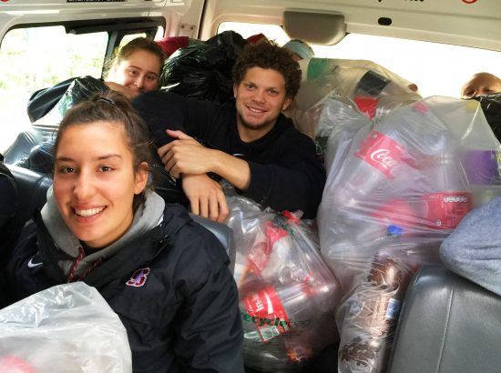 student athletes taking out trash in van