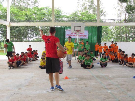 student-athlete teaaching basketball to kids