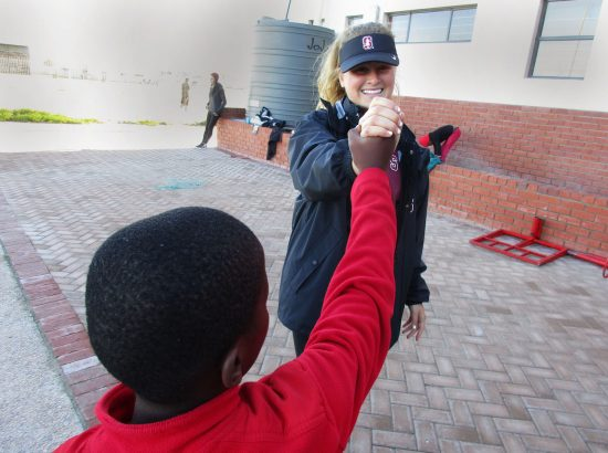 student athlete giving child high five outside