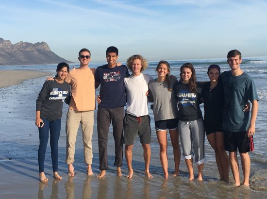 A group of student-athletes posing together on the beach