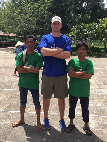 ACE Student-Athlete smiling with two of his students