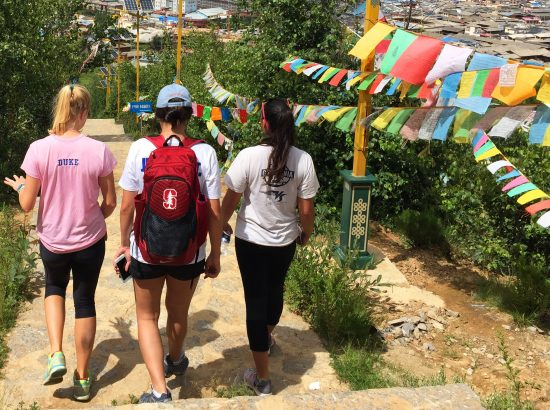 female student athletes walking down mountain in view of colorful prayer flags