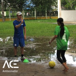 ACE participant playing soccer with child