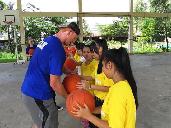 Young man helping girls properly hold a basketball