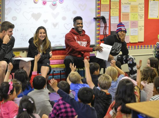 Students reading to children in classroom
