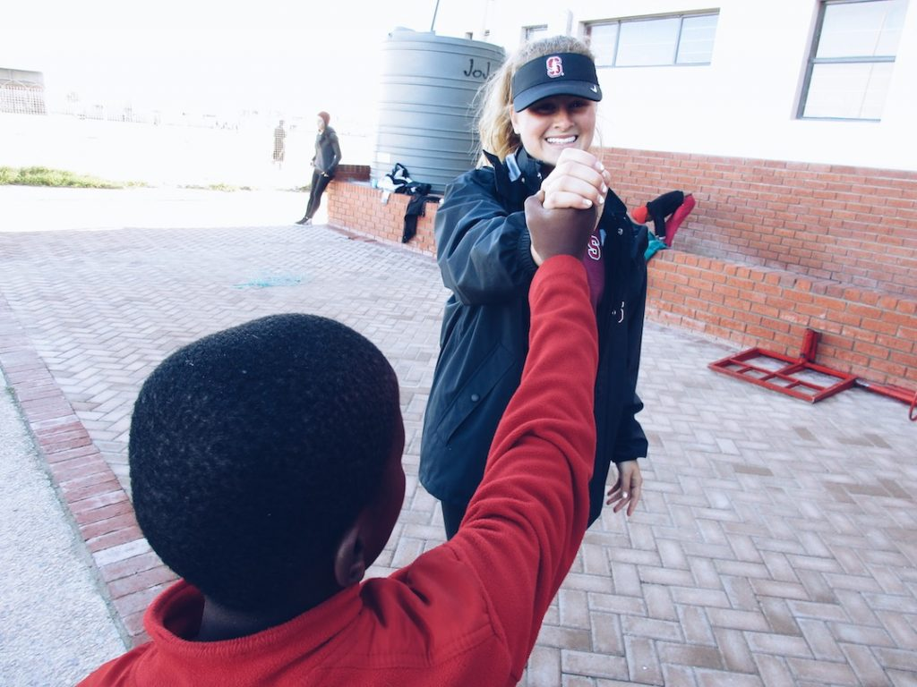 student-athlete high-fiving child outside