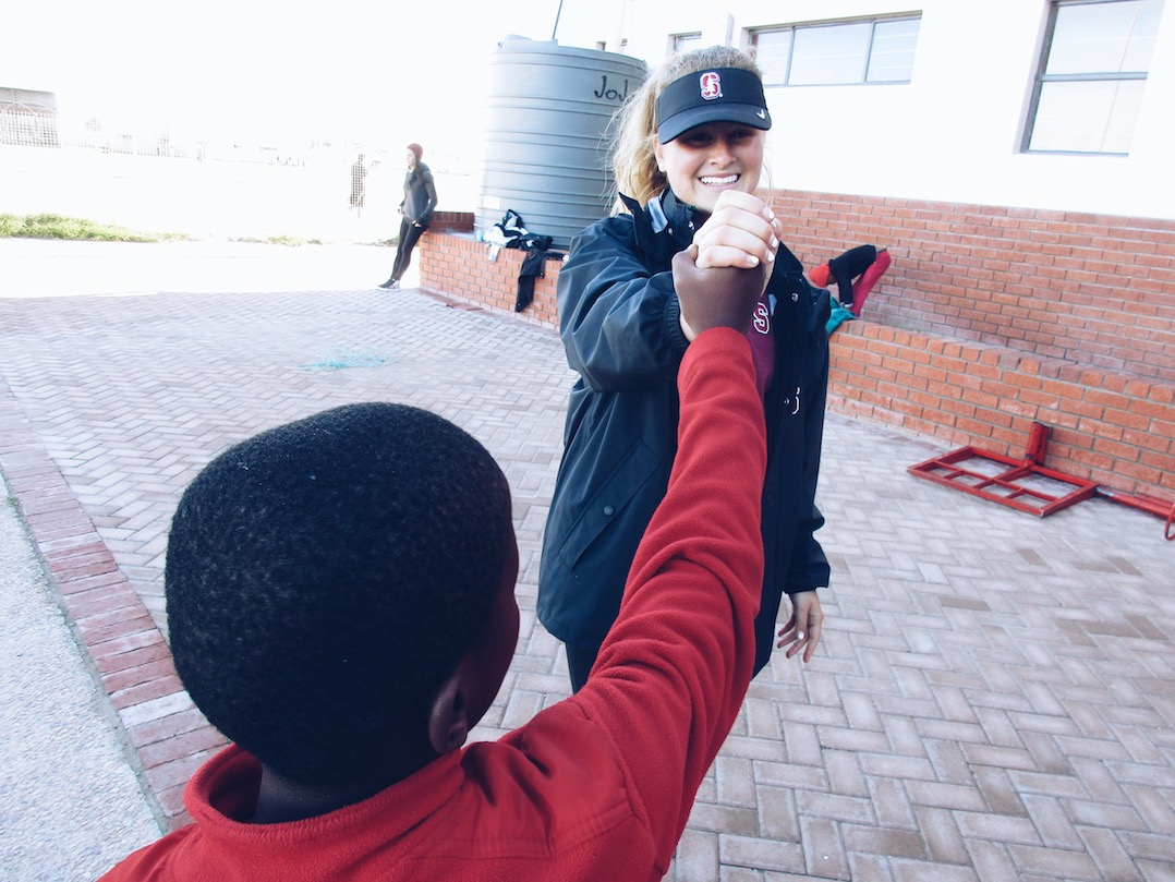 student-athlete smiling and high-fiving child outside