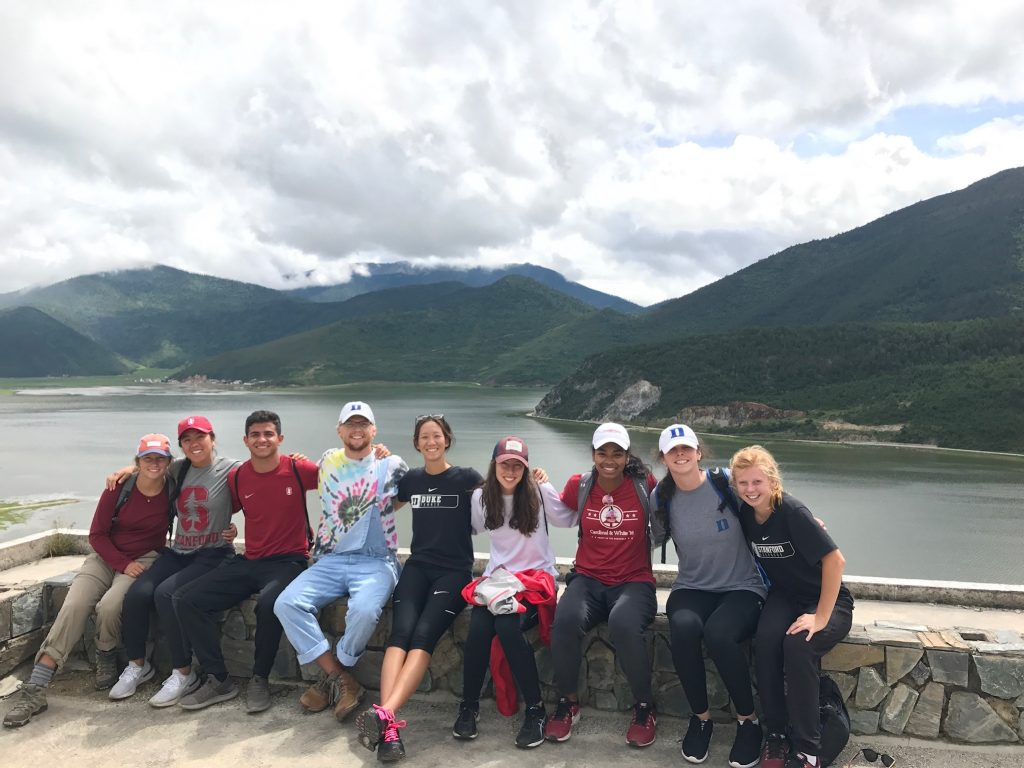 nine duke and stanford student-athletes sitting in front of a lake and mountains