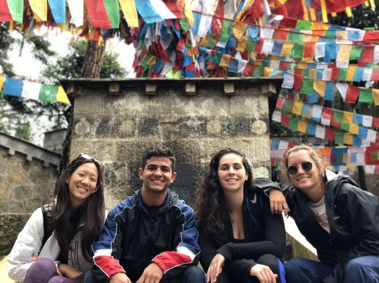 four students sitting behind stone monument and prayer flags
