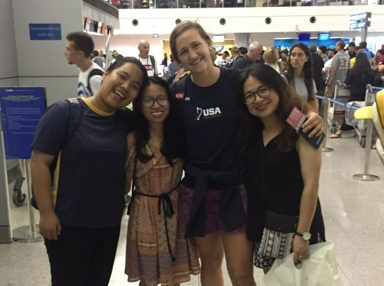 one American and three Vietnamese college students with arms around each other in the airport
