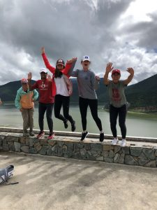 five female student-athletes jumping off a stone wall