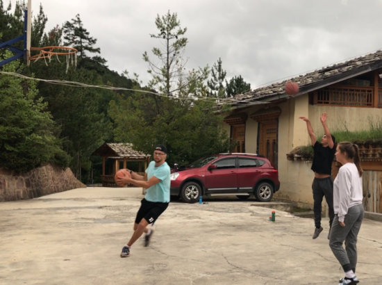 three people playing basketball outside