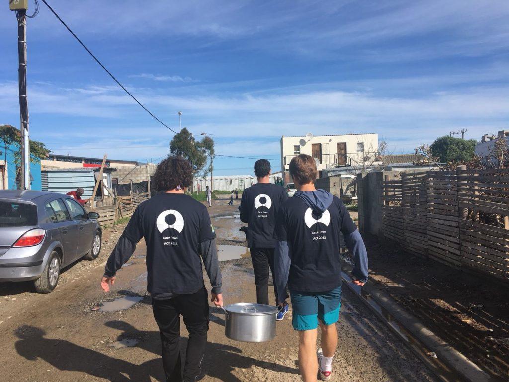 three students carrying big metal pots of food