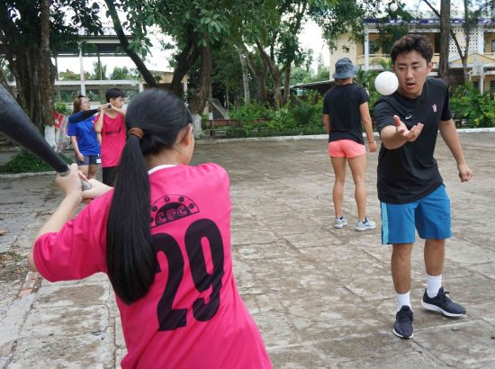 coach throwing baseball to student in Vietnam