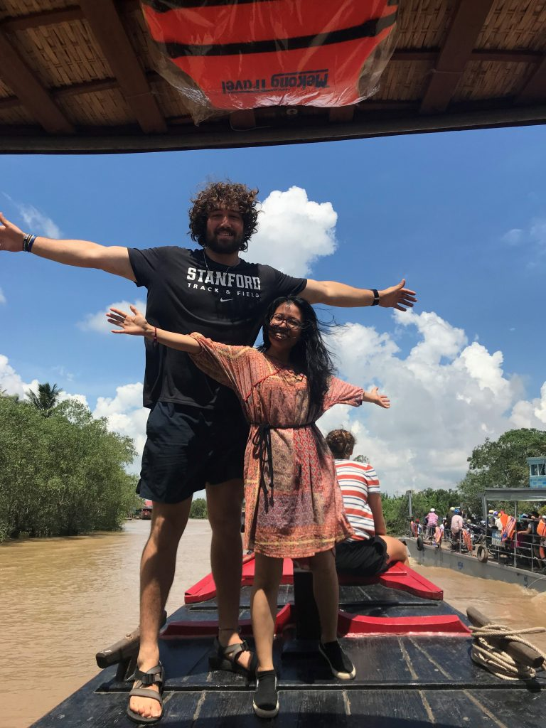 Two people stand on boat in middle of river