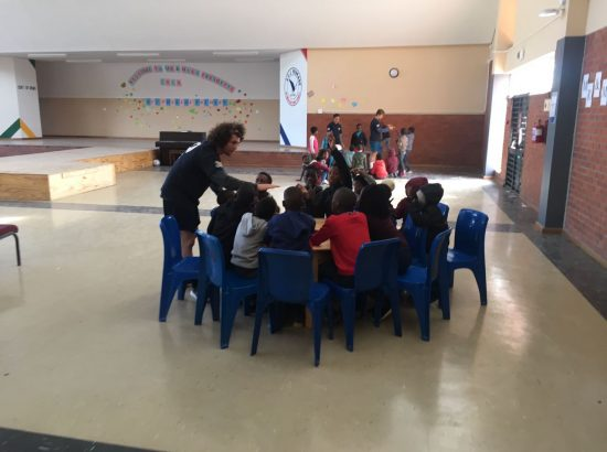 Teacher talking to students sitting at a table