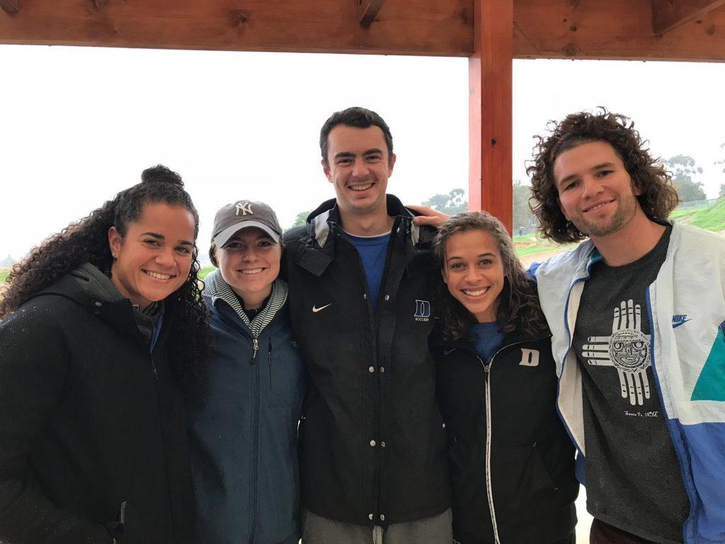 Group of Duke ACE athletes smiling in raincoats