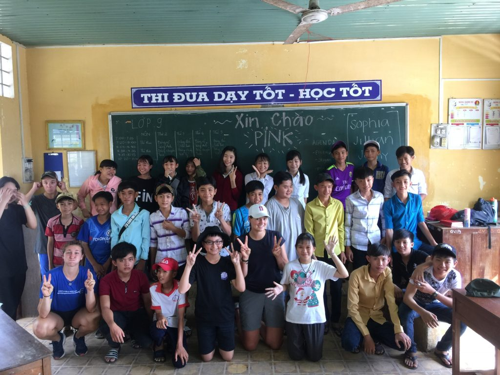 Students and Coaches pose in classroom