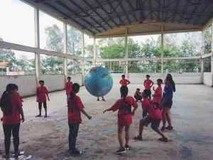 Students playing volleyball with giant globe