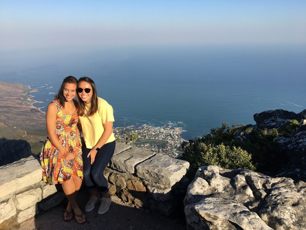 Sydnei and Aleeza sitting on a mountain with ocean in background