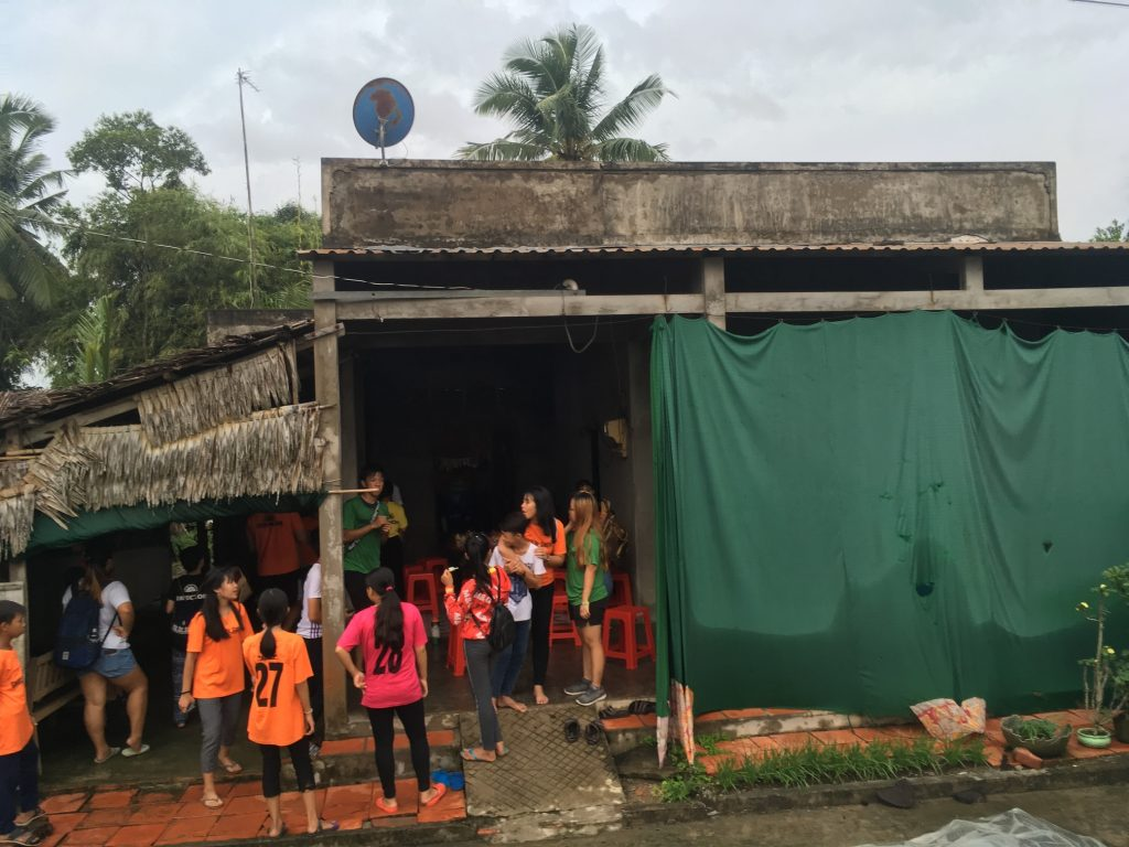 house in Vietnam with family and students standing in front