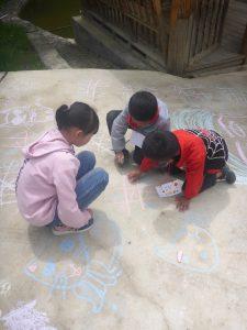 three kids drawing on sidewalk with chalk