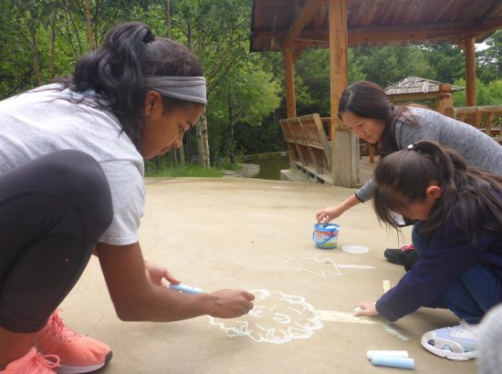 three people drawing with chalk