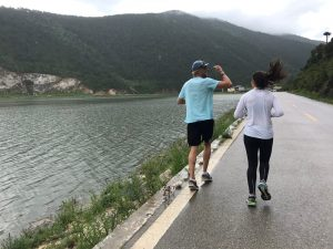 two people running along the lake