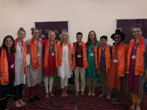 group of ten students wearing brightly colored orange scarves