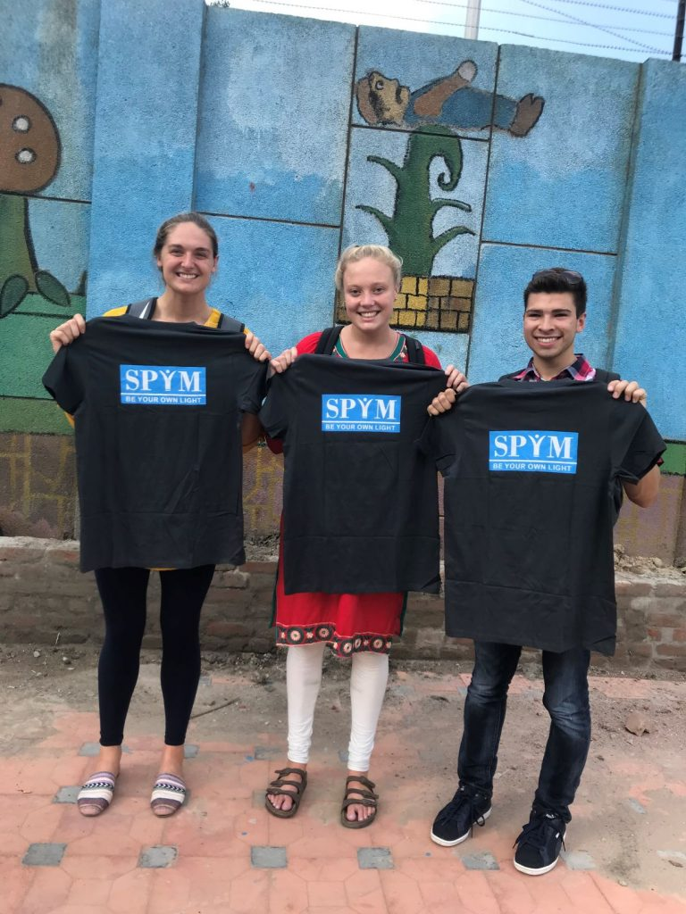 three students holding a t-shirt