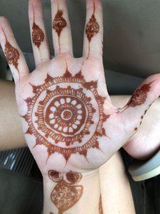 hand with brown henna art design