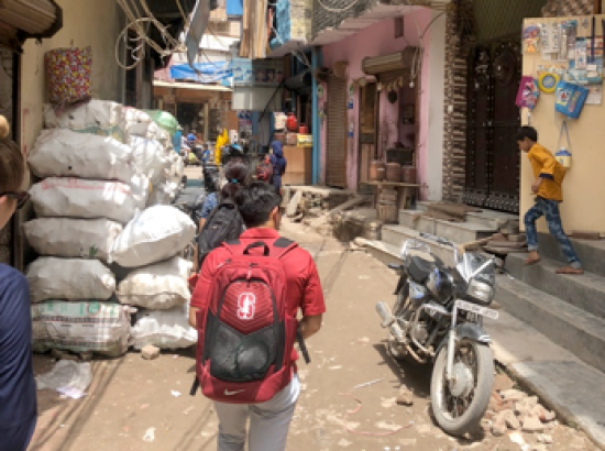 student walking with a backapack in a market