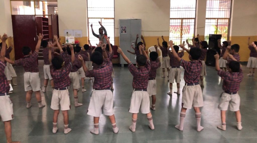 children dancing together with arms in the air