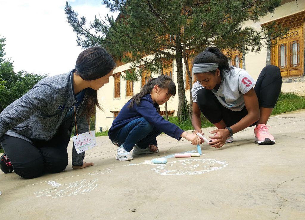 children and student-athletes playing with chalk outside