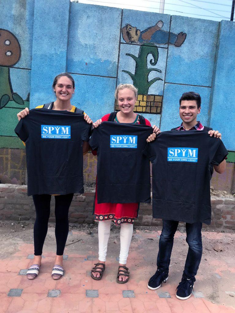 student-athletes holding t-shirts outside