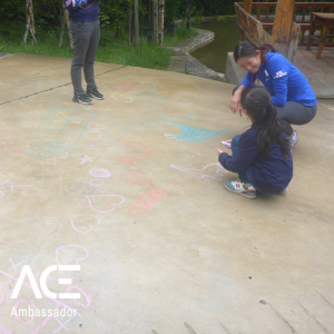student and child playing with chalk outside
