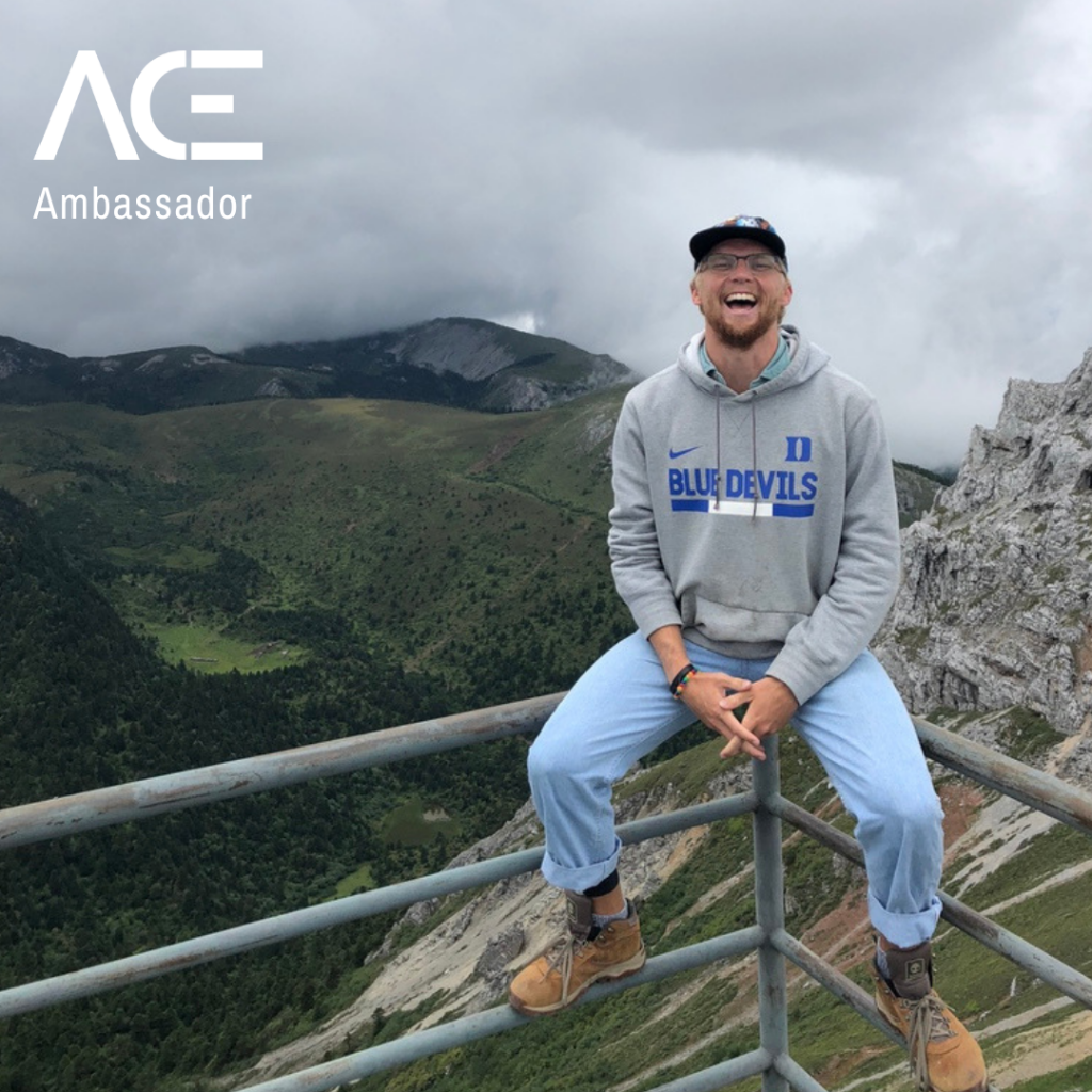 male student-athlete sitting on ledge overlooking mountain