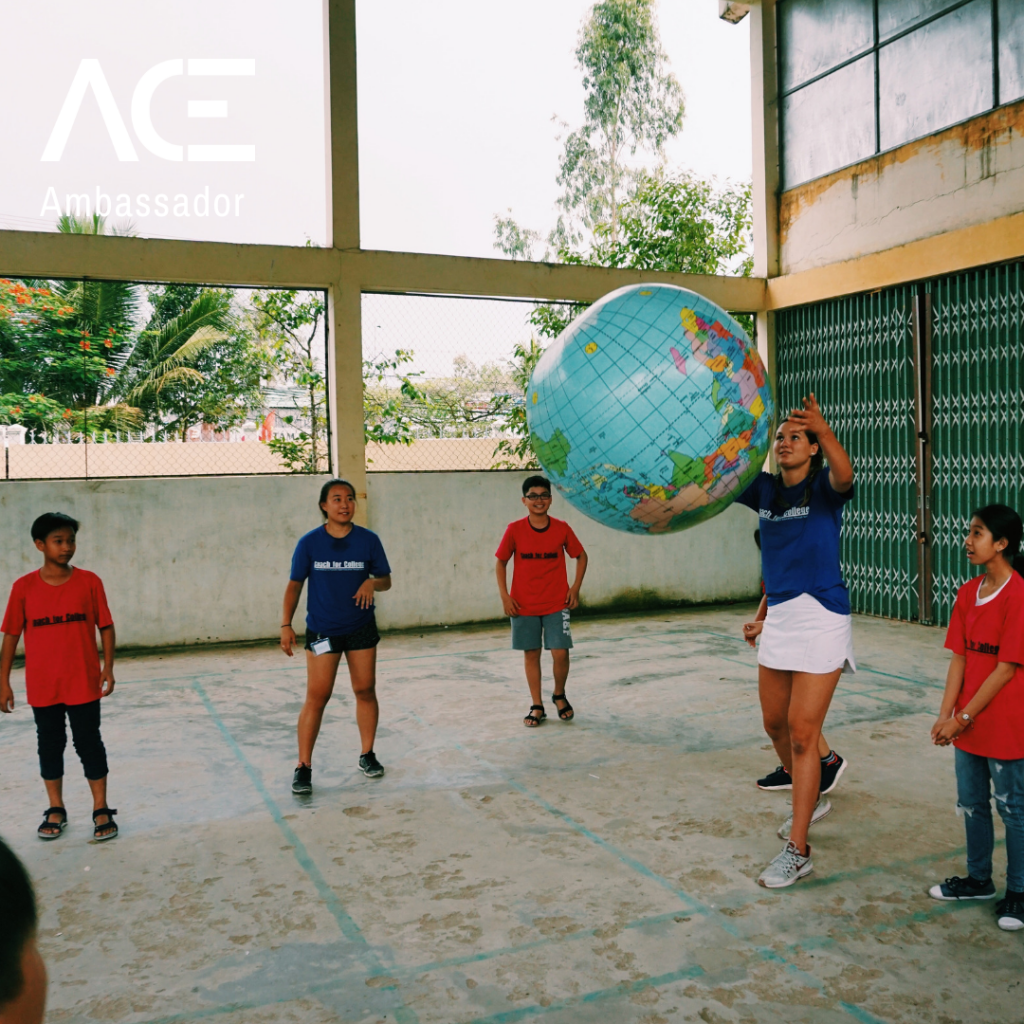 young adult throwing globe in circle with kids