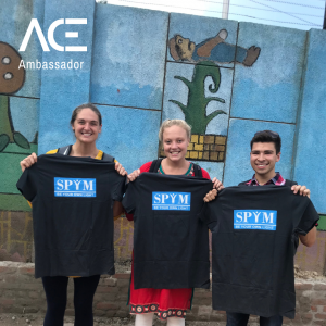 three young adults holding up an organization t shirt