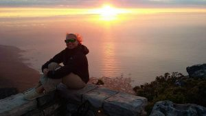lady sitting above ocean overlook at sunset