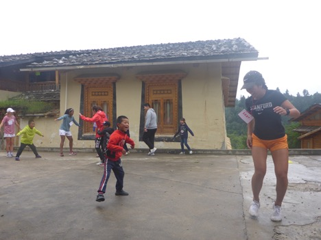 child and female student-athlete dancing outside