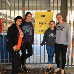 "group of women standing in front of sign that reads ""No Bully Zone"""