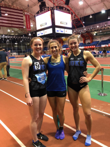 three female student-athletes standing and smiling on track field