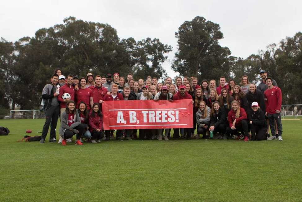 group of people in red shirts holding sign that reads a, b, trees on field