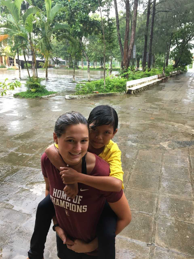 student-athlete giving kid piggyback ride outside in the rain
